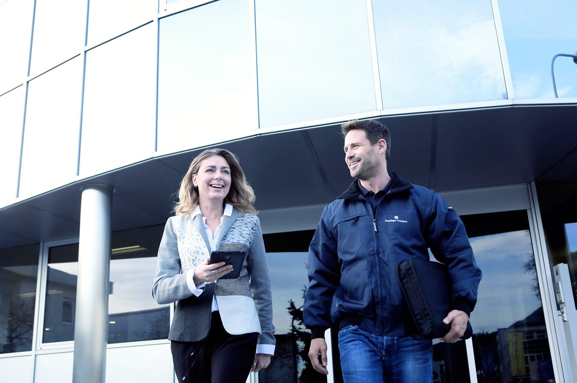 Ein Fluckinger Mitarbeiter und eine Kundin stehen vor dem Fluckinger Gebäude